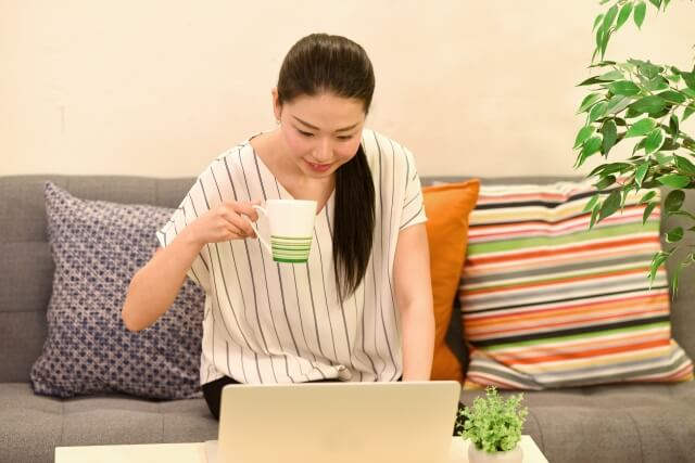 オンラインレッスン,自宅でソファーに座りパソコンを見ている女性