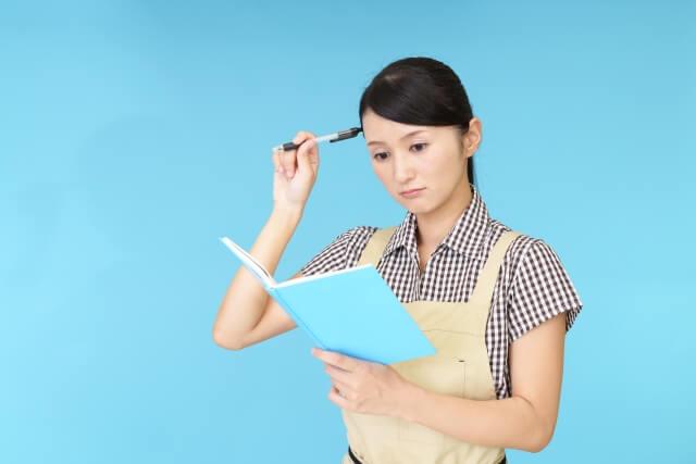 困った顔でノートをみる主婦