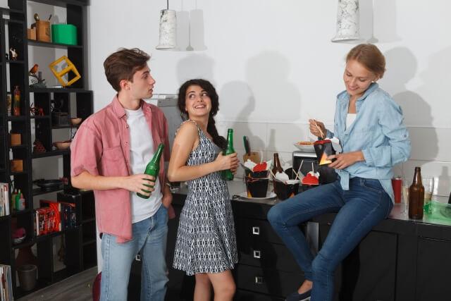 3人の若い男女がホームパーティで楽しくお酒を飲む様子